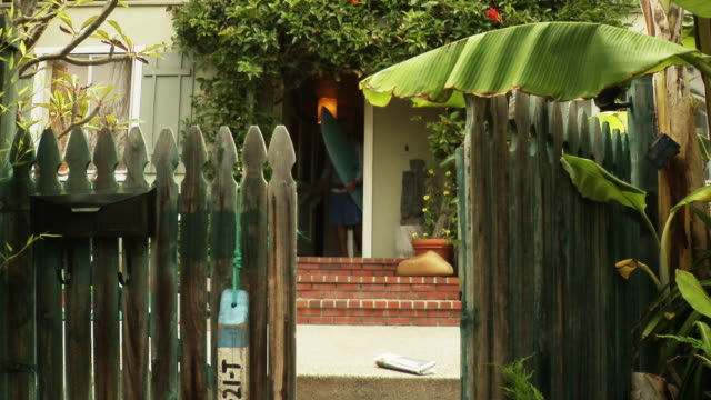 ms man leaving house carrying surfboard and picking up newspaper from front yard, laguna beach, california, usa - laguna beach california video stock e b–roll