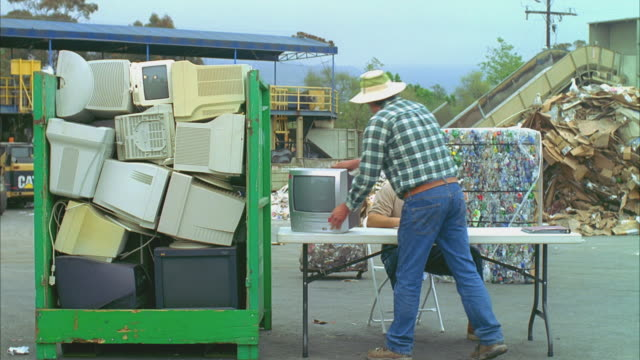 ws man leaving old tv set in recycling center, santa barbara, california, usa  - e waste stock videos & royalty-free footage