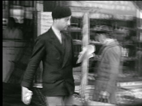 B/W 1927 MS PAN man leaving shop carrying baguette + walking on sidewalk / Paris, France