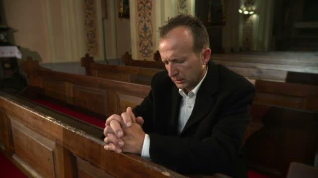 hd: mann verlassen sie die kirche nach einem gebet - kreuzbein stock-videos und b-roll-filmmaterial