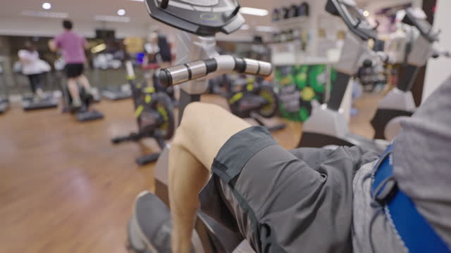 man leg cycling on exercise bike in gym. - wide shot stock videos & royalty-free footage