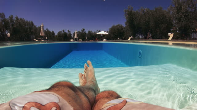 man pov legs crossed relaxing point of view: in a swimming pool at summer - sunbathing stock videos & royalty-free footage