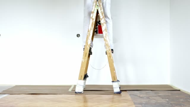 man legs standing on a ladder painting the wall - diy stock videos & royalty-free footage