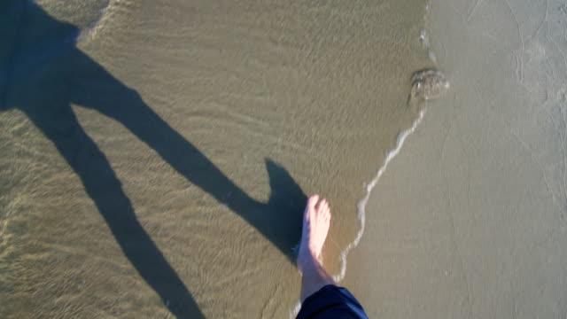 vídeos de stock, filmes e b-roll de pernas de homem andando numa praia - ponto de vista de caminhada
