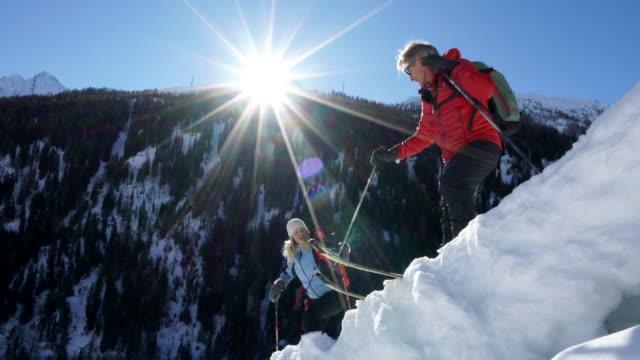 man leiht teamkollege skifahren verschneiten grat hand - skijacke stock-videos und b-roll-filmmaterial