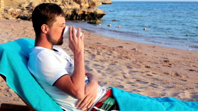 vídeos de stock, filmes e b-roll de o homem encontra-se em um deckchair e bebe o chá. descanse no mar. - copo descartável