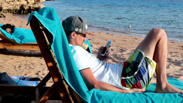 Man lies on a deckchair and using a smartphone for work.