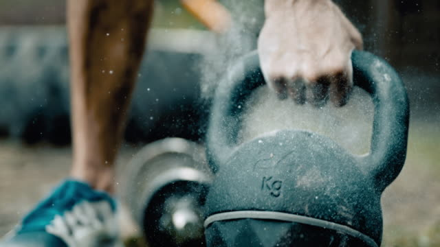 vídeos de stock e filmes b-roll de super slo mo man lifting a heavy kettlebell - body building