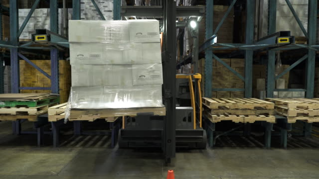 Man lifting and placing pallet on shelving by forklift in warehouse