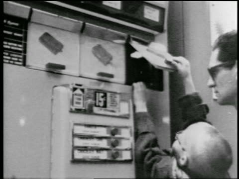 b/w 1957 man lifting boy to help him get ice cream bar from vending machine - ice cream bar stock videos and b-roll footage