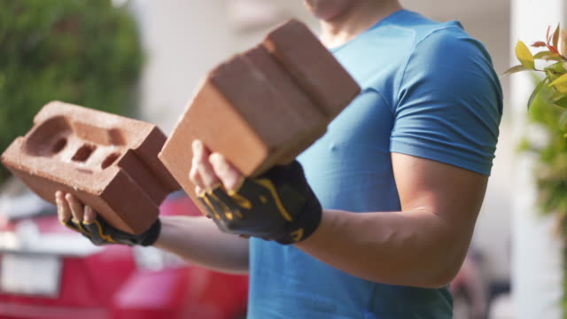 man lifting bricks as weights training at home. - relaxation exercise stock videos & royalty-free footage