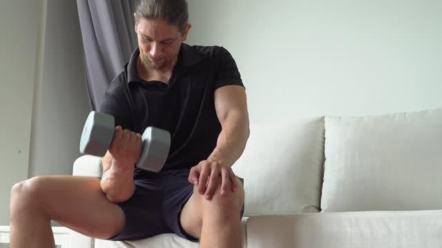 mann hebt hantel, während er zu hause auf der bank sitzt - trainingsraum wohnraum stock-videos und b-roll-filmmaterial