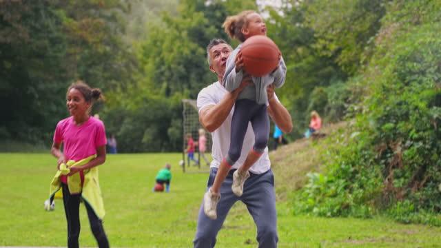 vidéos et rushes de homme soulevant ses filles dans l'air pour jeter un cerceau et marquer - panier de basket