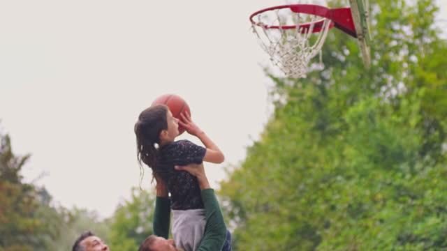 vidéos et rushes de homme soulevant son fils dans l'air et il jette le basket-ball et marque - panier de basket