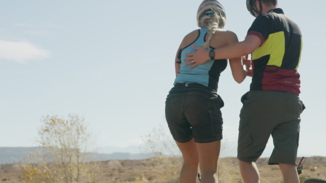 man lifting injured woman then leaving pushing mountain bikes / caineville, utah, united states - pushing stock videos and b-roll footage