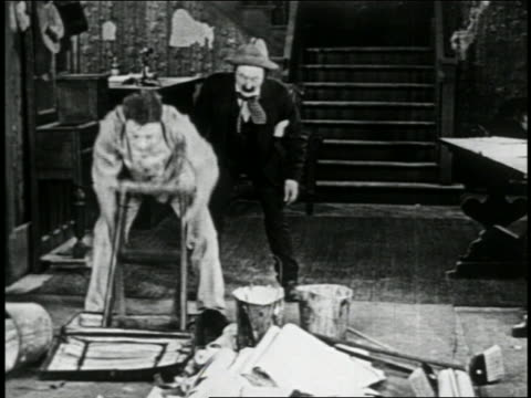 stockvideo's en b-roll-footage met b/w 1915 man lifting ladder from hole in floor / hits man in background repeatedly / short - 1915