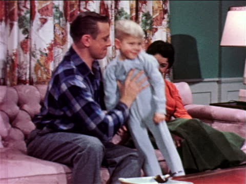 1957 man lifting small boy to couch / family watching offscreen television / industrial