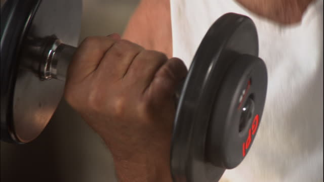 A man lifts a dumbbell in a bicep curl.