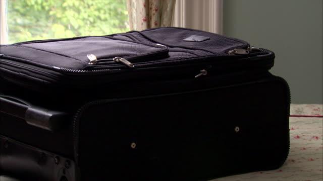 vídeos y material grabado en eventos de stock de a man lifts a packed suitcase off his bed. - maleta