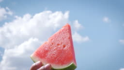 A Man Lifts a Watermelon Slice into the Summer Sky