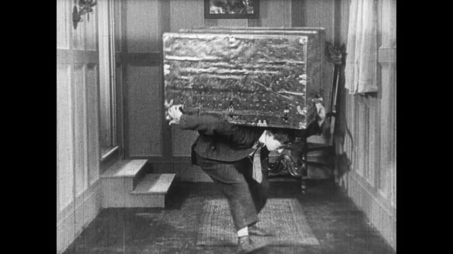 1922 man (buster keaton) lifts trunk with woman inside - sollevare video stock e b–roll