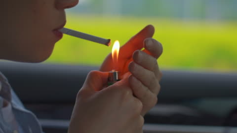 man lighting a cigarette inside the car - cigarette stock videos & royalty-free footage