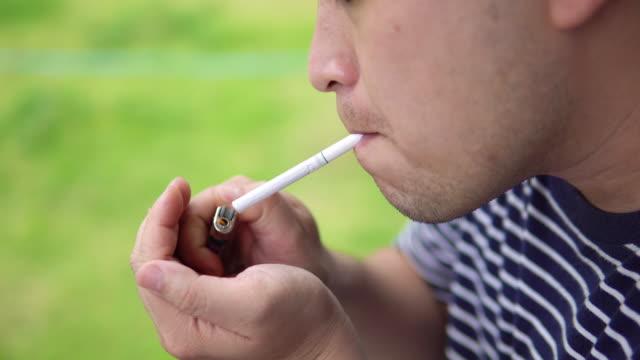 vídeos y material grabado en eventos de stock de hombre encendiendo cigarrillos con encendedor e intentos de fumar. - boquilla producto relacionado con el tabaco