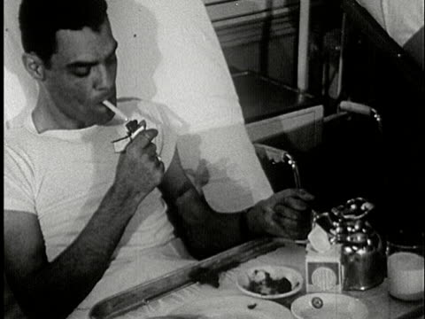 MS, B/W, Man lighting up cigarette sitting in hospital bed, USA