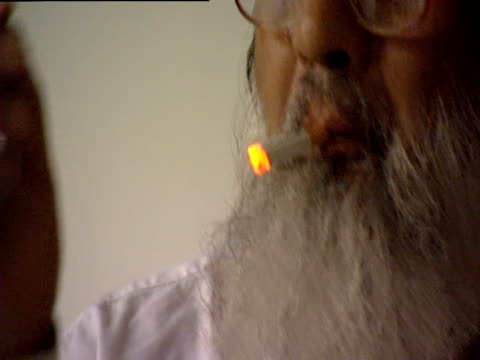 man lights cigarette with match and wipes his brow - マッチ箱点の映像素材/bロール