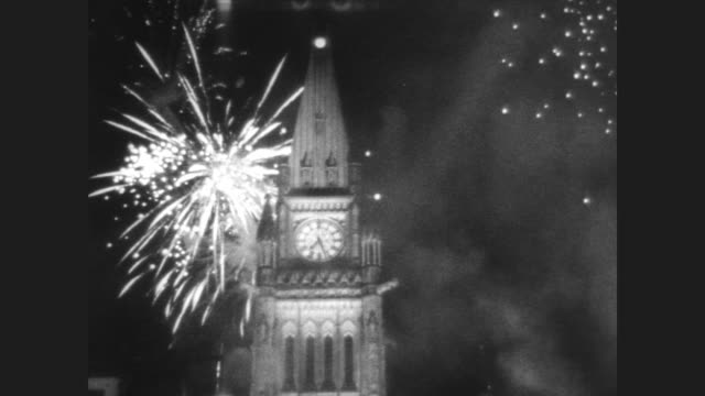 man lights giant flame with torch on parliament hill signaling start of canada's centennial celebrations / fireworks explode behind peace tower /... - parliament hill stock videos & royalty-free footage