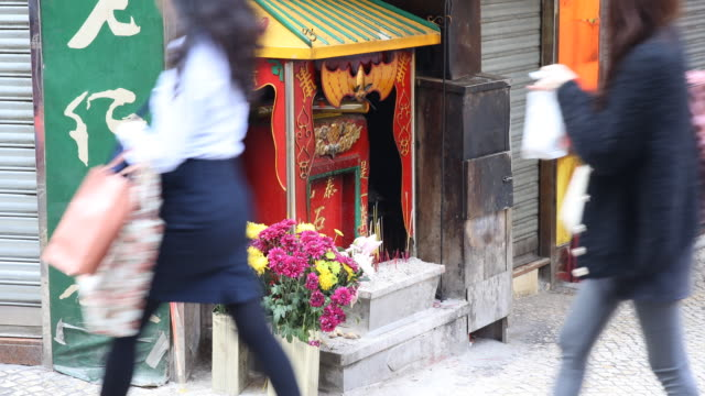 a man lights incense at a buddhist mini altar with burning incenses at the street - ein tag im leben stock-videos und b-roll-filmmaterial
