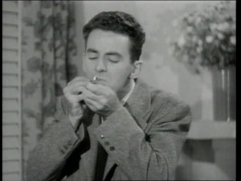 1942 montage man lights up cigarette but burns himself  - match lighting equipment stock videos & royalty-free footage