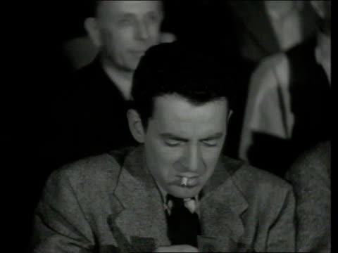 1942 montage man lights up cigarette in theater, drawing the attention of an usher - usher stock videos & royalty-free footage