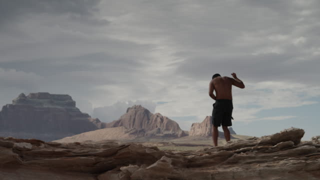 ws ds man listening music and dancing on rocks near lake powell / utah, usa - lago powell video stock e b–roll
