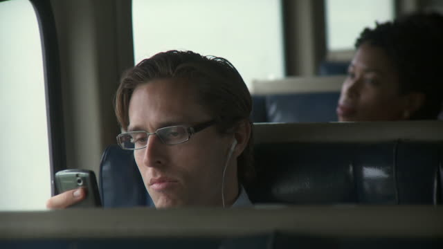 CU Man listening music on portable media player and looking at mobile phone in moving commuter train / New York City, New York, USA