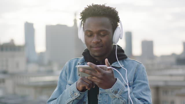 man listening music on roof. changing songs on smartphone - african american culture stock videos & royalty-free footage