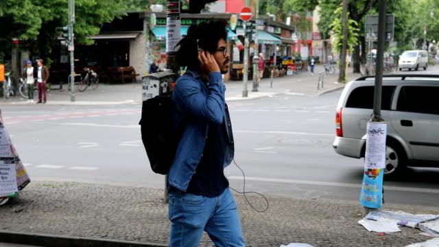 menschen hören musik über kopfhörer auf bürgersteig - rucksack stock-videos und b-roll-filmmaterial