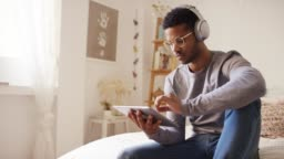 Man listening music while using digital tablet
