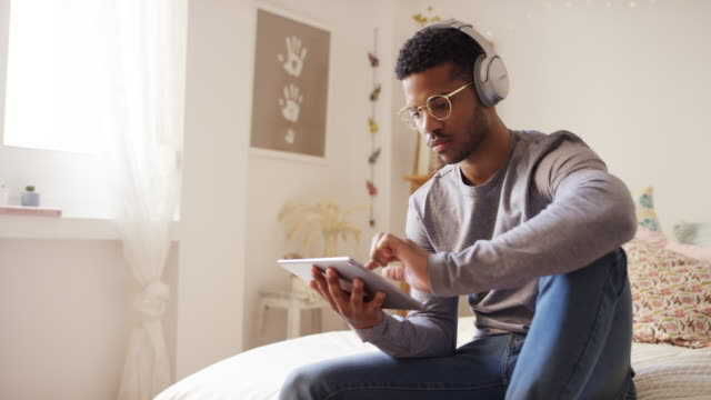 vídeos de stock e filmes b-roll de man listening music while using digital tablet - afro