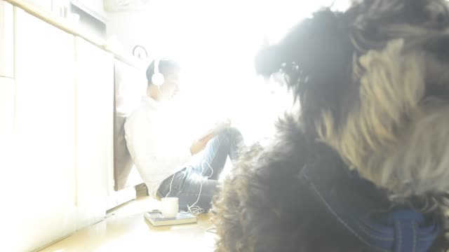 man listening music with digital tablet in kitchen at home with dog - 床に座る点の映像素材/bロール