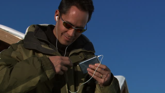 man listening to mp3 player and putting on his gloves - ski jacket stock videos & royalty-free footage