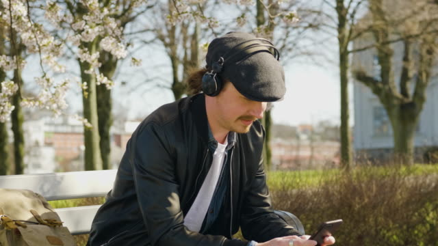 man listening to music in the park - headphones stock videos & royalty-free footage