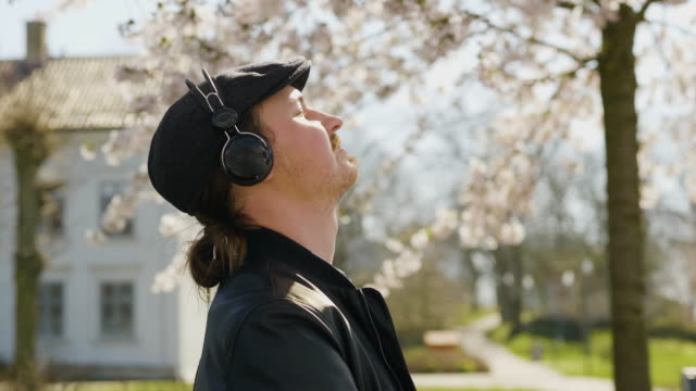 man listening to music in the park with enjoyment - headphones stock videos & royalty-free footage