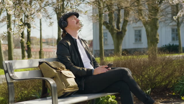 man listening to music in the park with enjoyment - bench stock videos & royalty-free footage