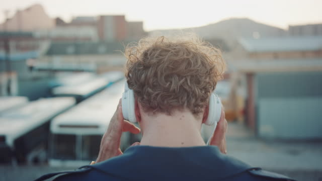 man listening to music on rooftop - headphones stock videos & royalty-free footage