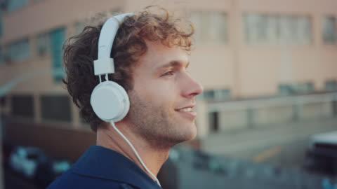 vidéos et rushes de un homme écouter de la musique sur le toit - casque