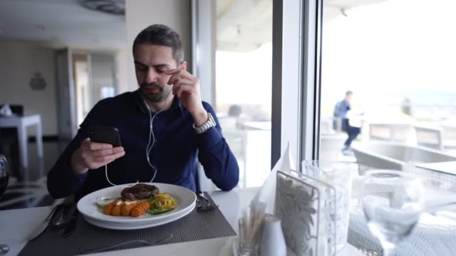 man listening to podcast on lunch break - lunch break stock videos & royalty-free footage