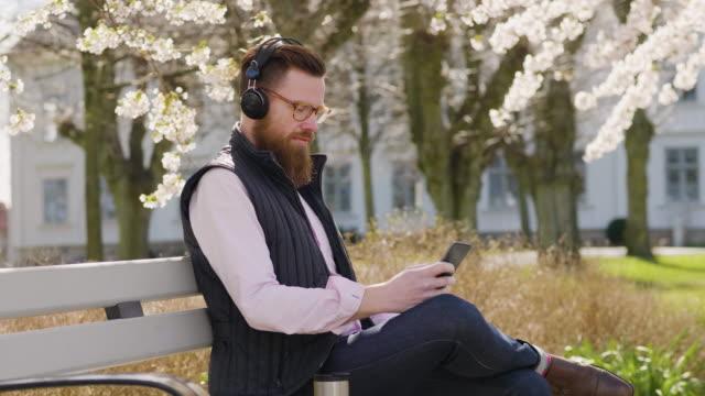 stockvideo's en b-roll-footage met mens die aan podcasts op zijn slimme telefoon luistert - springtime
