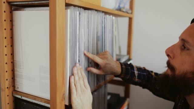 レコードプレーヤーでビニールレコードを聴いている人 - ミュージックショップ点の映像素材/bロール