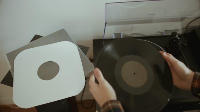 man listening vinyl records with a record player - hi fi video stock e b–roll